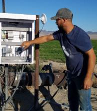 Operator managing controls on solar powered irrigation in Railroad Valley, Nevada.