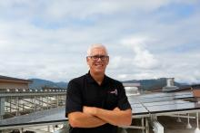 Bruce Hanna, owner of Hampton Inn and Suites Roseburg, visits solar panels recently installed on hotel roof.